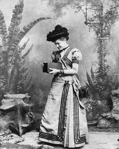 A woman holds an early Kodak camera which was sold with the film already loaded